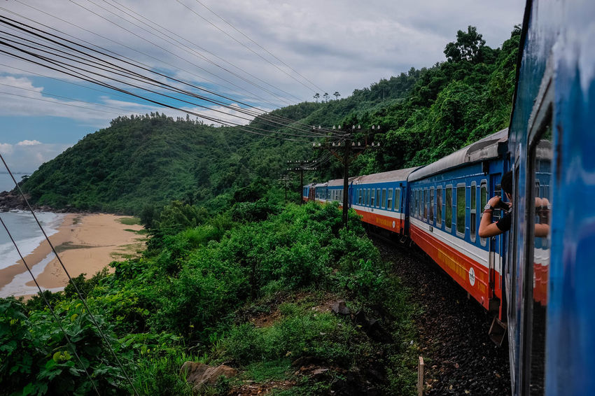 On board of the Reunification Express. Taking Photos Vietnam Cloud - Sky Day Electricity  Green Color Journey Land Vehicle Mode Of Transportation Nature Ocean Outdoors Passenger Train Plant Public Transportation Rail Transportation Railroad Track Sky Track Train Train - Vehicle Transportation Travel Tree