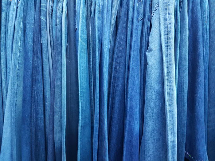 Full Frame Shot Of Blue Jeans Pants For Sale At Clothing Store