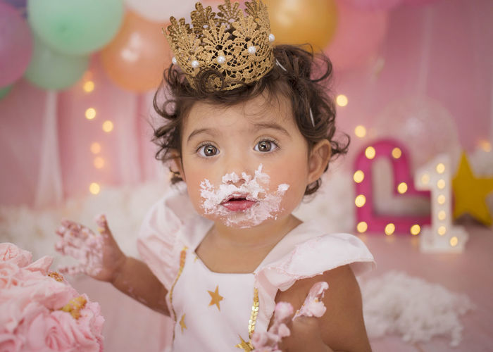 Cute baby girl with balloons and birthday cake sitting at home