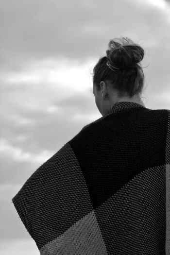 Rear view of woman wrapped in blanket standing against sky