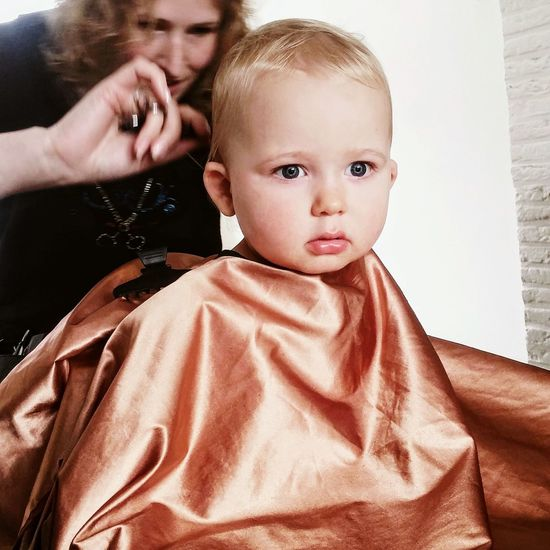 Female hairdresser cutting baby boy hair at hair salon