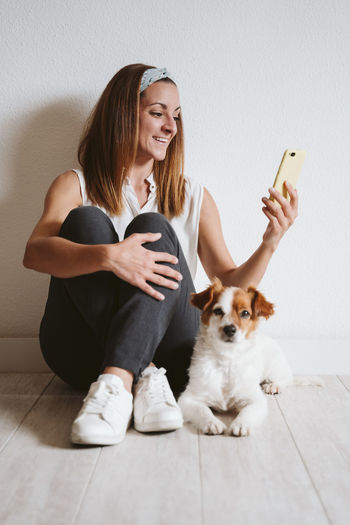 Young woman holding dog while sitting at home