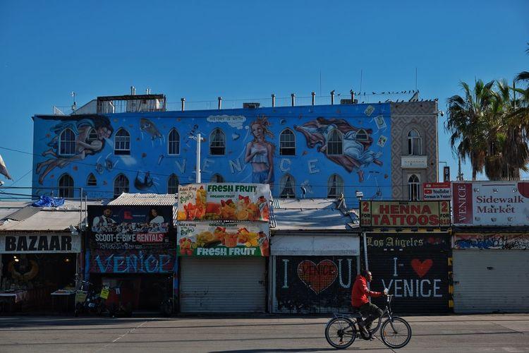 Graffiti on wall by street against blue sky