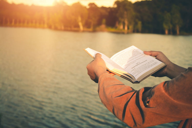 Midsection of man holding book against sea during sunset