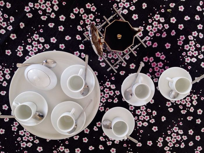 High angle view of empty cups and saucers by espresso maker on table
