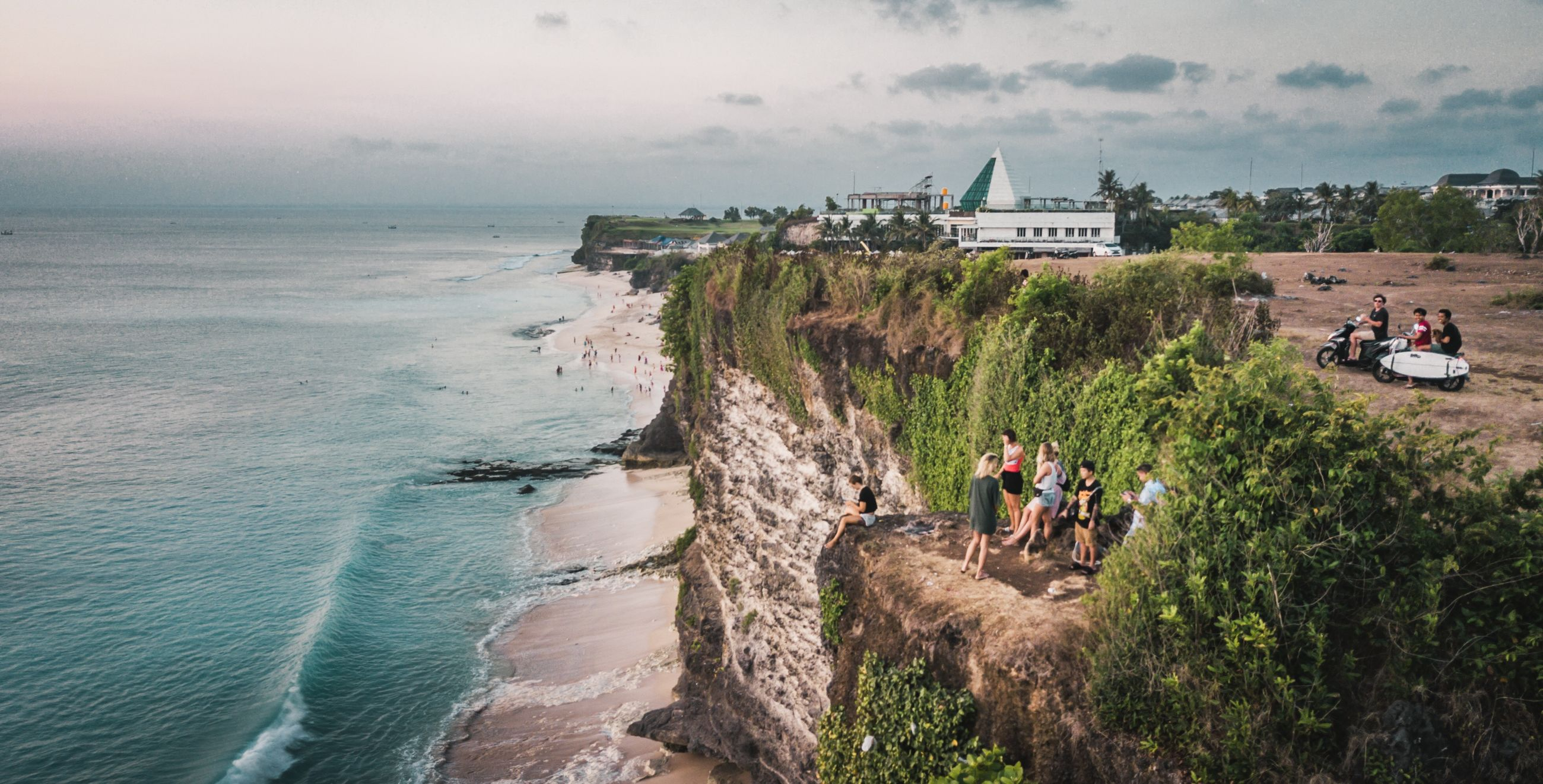 sea, water, land, sky, beach, architecture, group of people, nature, scenics - nature, real people, beauty in nature, men, built structure, people, building exterior, motion, day, cloud - sky, plant, horizon over water, outdoors