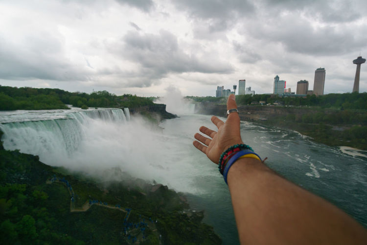Cropped Hand Of Man Reaching Towards Against Niagara Falls