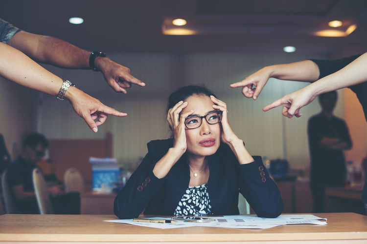 Colleagues Pointing At Frustrated Businesswoman Sitting At Desk In Office