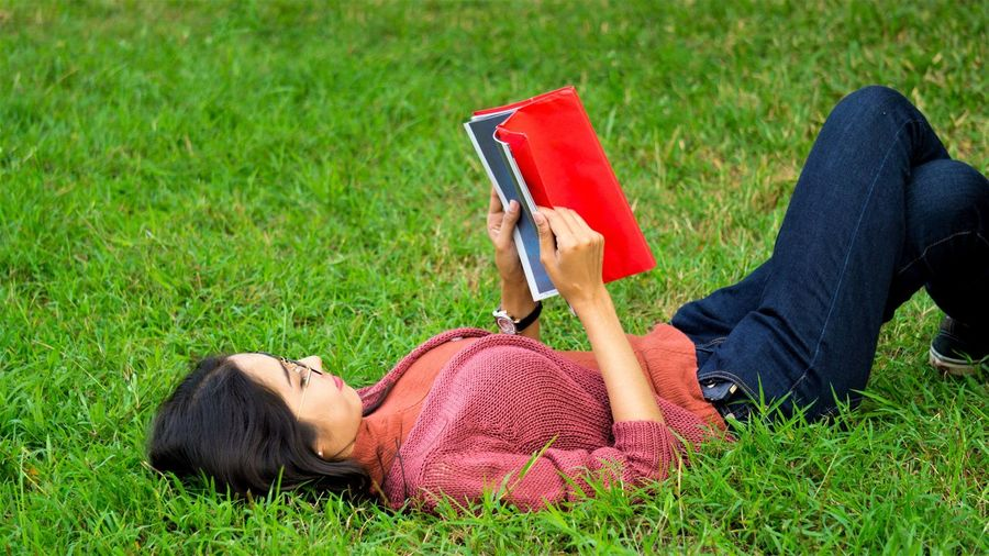 Young woman reading book while lying on grassy field