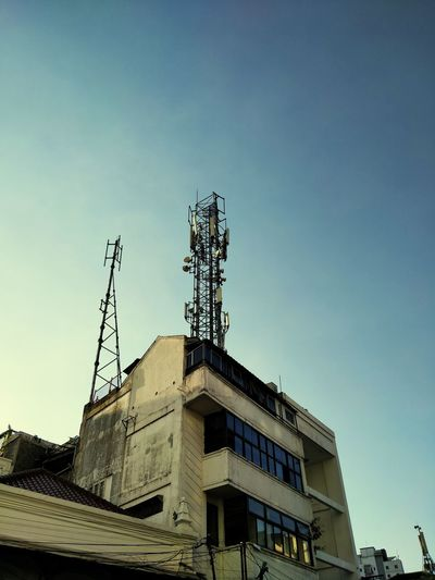 Low angle view of communications tower and building against clear sky
