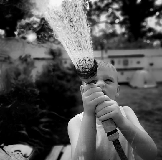 Boy spraying water with garden hose