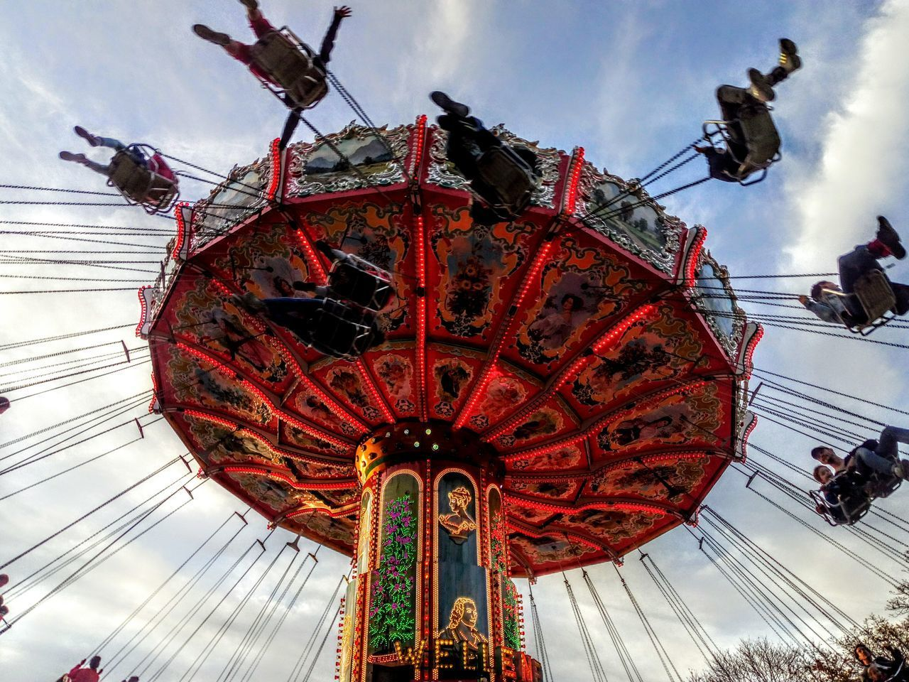 amusement park, amusement park ride, low angle view, arts culture and entertainment, chain swing ride, group of people, sky, cloud - sky, leisure activity, real people, fun, enjoyment, motion, day, nature, medium group of people, incidental people, men, spinning, outdoors, fairground