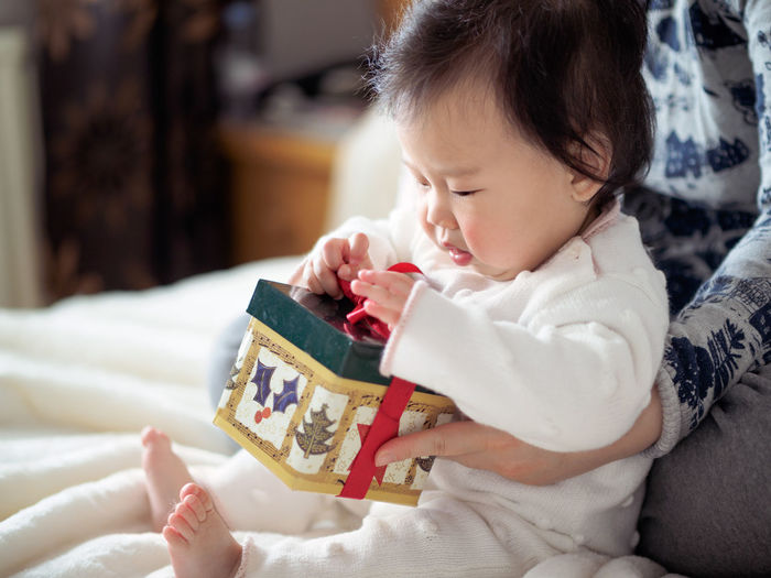 Asian baby girl get her first Christmas gift box Christmas Gift Box Asian Baby Girl Childhood Christmas Decoration Christmas Gift Close-up Cute Day Gift Holding Home Interior Human Hand Indoors  Lifestyles One Person People Real People Unwrapping