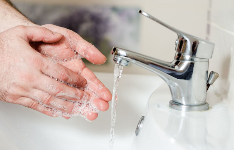Midsection of man with faucet in bathroom