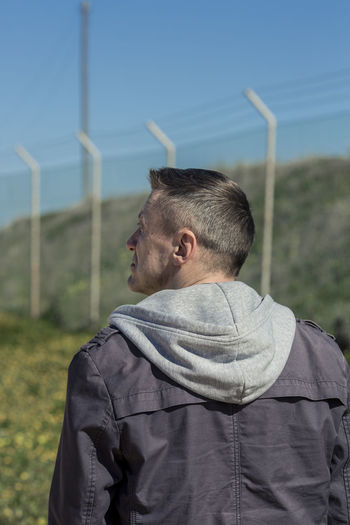 Rear view of adult man against barbed wire. 45-50 Barbed Wire HERO Adult Day Detective Environment Fence Field Focus On Foreground Headshot Hood - Clothing Land Landscape Leisure Activity Lifestyles Males  Men Nature One Person Real People Rear View Rural Scene Sky Strong