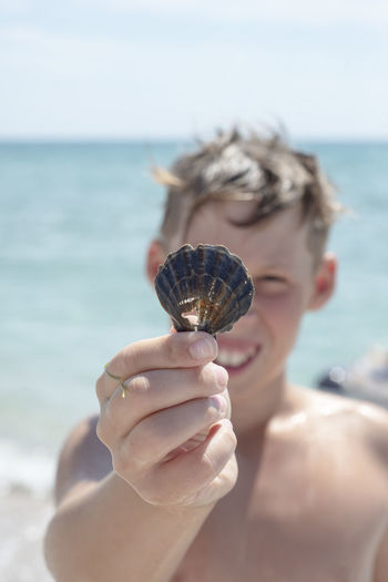 A boy against the background of the sea holds a shell with a hole in his hand. smile.