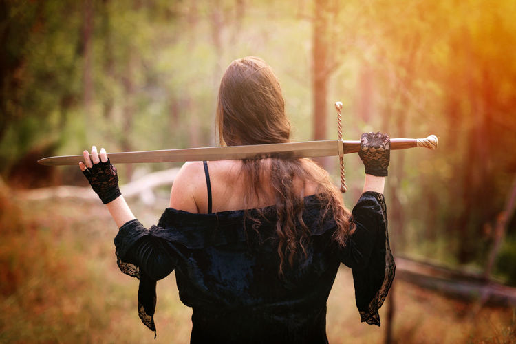 Back View Day Focus On Foreground Holding Leisure Activity Lifestyles Outdoors Photography Themes Story Sword Woman