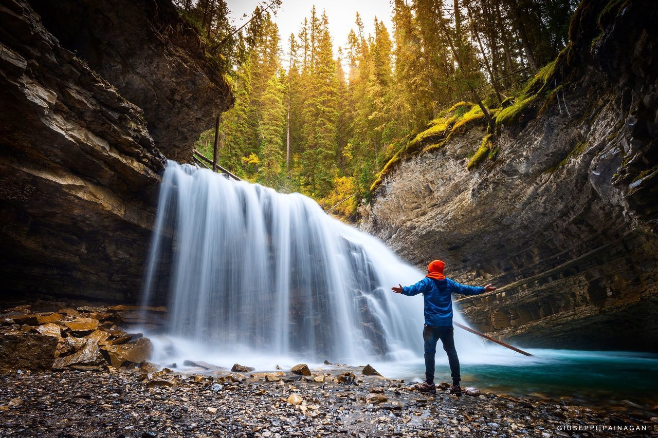 waterfall, motion, long exposure, flowing water, water, beauty in nature, nature, forest, standing, full length, casual clothing, scenics, one person, rock - object, real people, tree, blurred motion, tourism, day, holding, outdoors, adventure, lifestyles, young adult, people