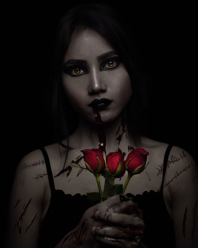 Close-up portrait of spooky young woman holding red rose against black background