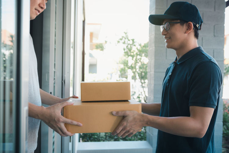 Delivery person giving packages on man while standing at entrance
