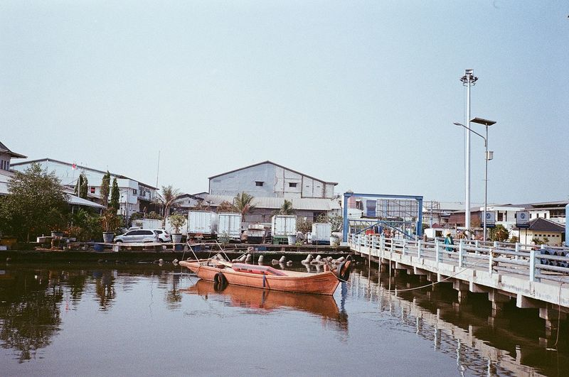 Boats moored in lake against buildings in city