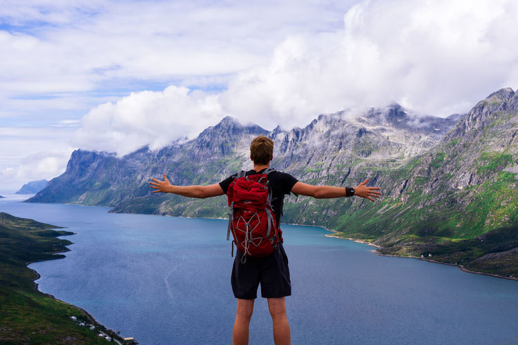 Rear View Of Man With Arms Outstretched Standing At Lakeshore Against Mountains