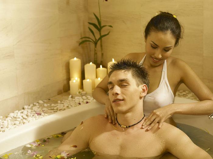 Close-Up Of Woman Massaging Man In Bathtub
