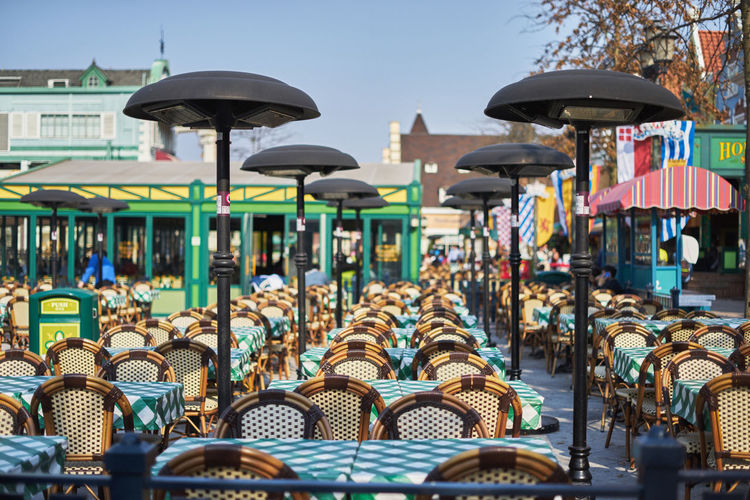 Street Light Amidst Empty Chairs And Tables At Sidewalk Cafe