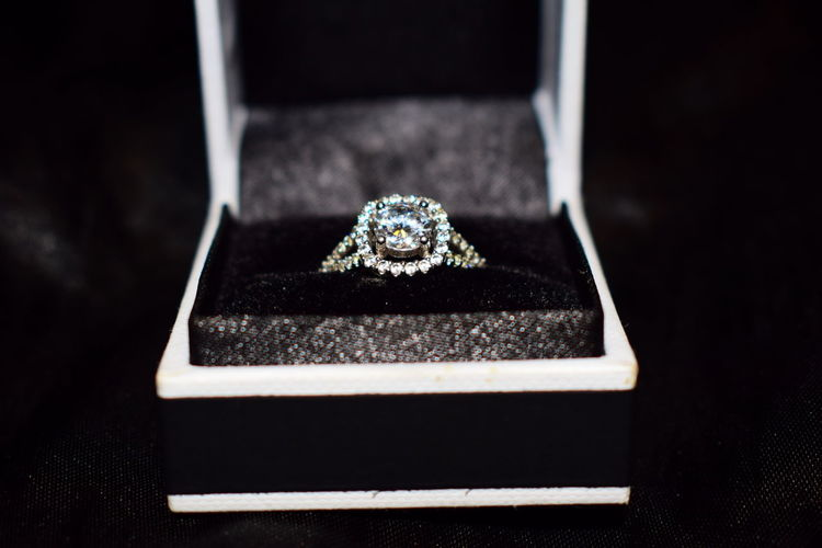 Close-up of diamond ring in box on black background