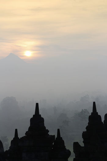 Silhouette Borobudur Temple with the mysteries forest surrounding during sunrise, Yogyakarta, Indonesia Ancient Borobudur Temple Java Yogyakarta Ancient Ancient Civilization Architecture Architecture And Art Belief Buddhism Built Structure Dawn Fog Forest History Mount Merapi Nature No People Place Of Worship Religious Architecture Sky Spirituality Sunrise Sunset The Past