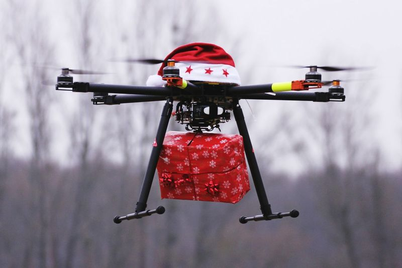 Drone with santa hat carrying christmas present against sky