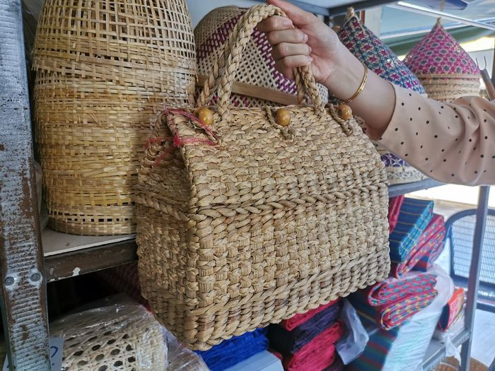 Cropped hand holding basket in store
