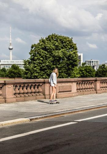 Full Length Of Woman Skateboarding On Road In City Against Sky
