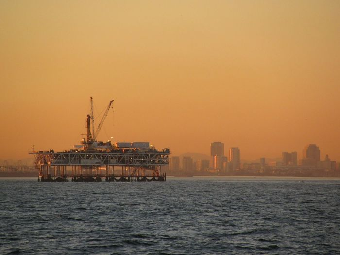 Offshore Platform Amidst Sea Against Orange Sky