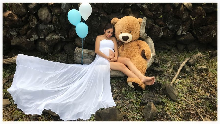 Pregnant woman sitting by balloons and stuffed toy on rock