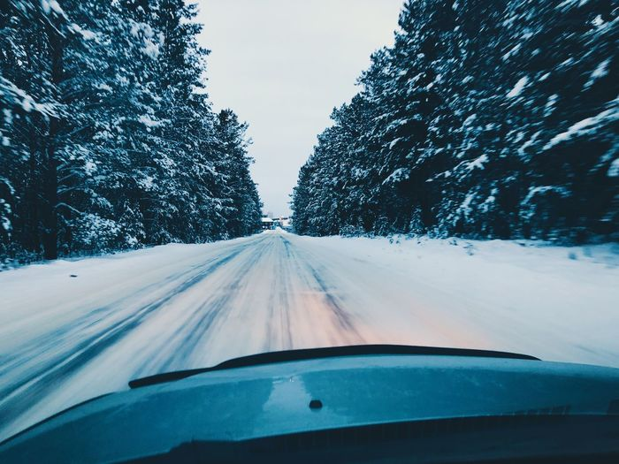 Snow covered road seen through car windshield during winter