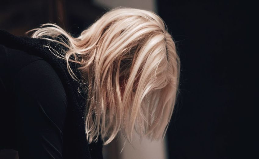 Close-up of woman with blond hair bending