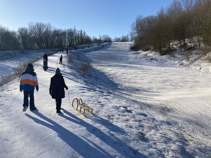 Rear view of people on snow covered field