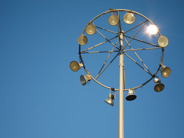 Low Angle View Of Illuminated Floodlight Against Clear Blue Sky