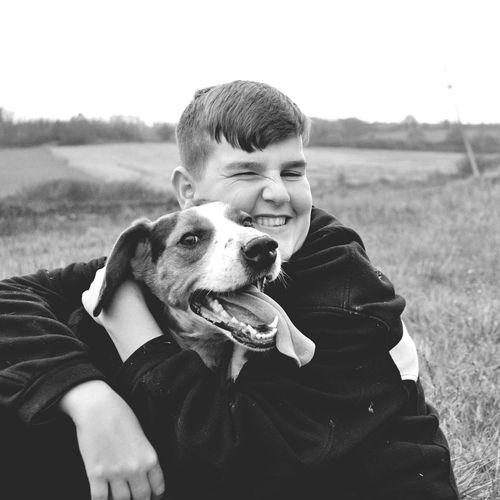 Portrait of boy with dog sitting on field
