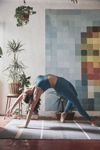 Woman sitting on floor against wall at home
