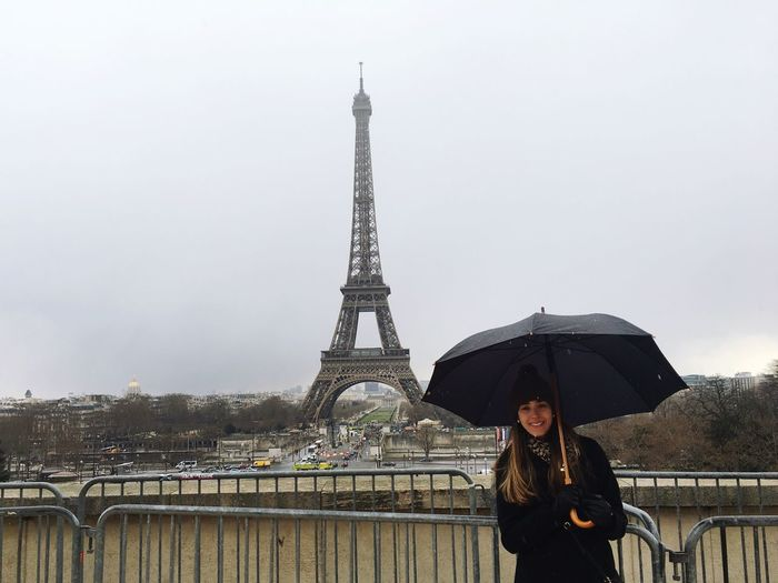 Young woman holding umbrella standing against eiffel tower in city during winter
