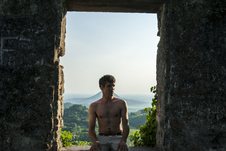 Shirtless man sitting on window sill against sky