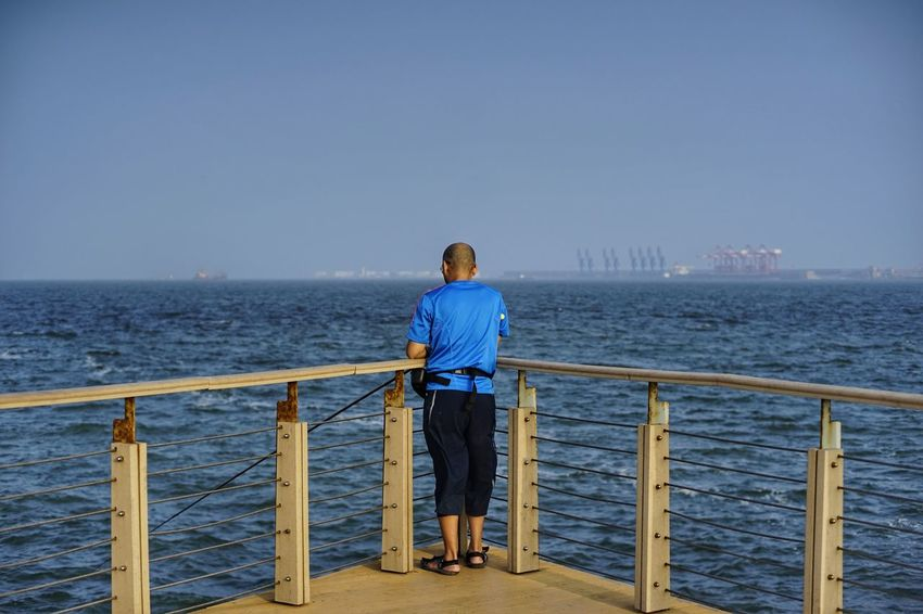 Fishing Equipment Fishing Rod Fish Fishing Water Sea Full Length Clear Sky Beach Standing Blue Front View Mid Adult Sky Hooded Shirt Pier Horizon Over Water Seascape Ocean Coast Tide