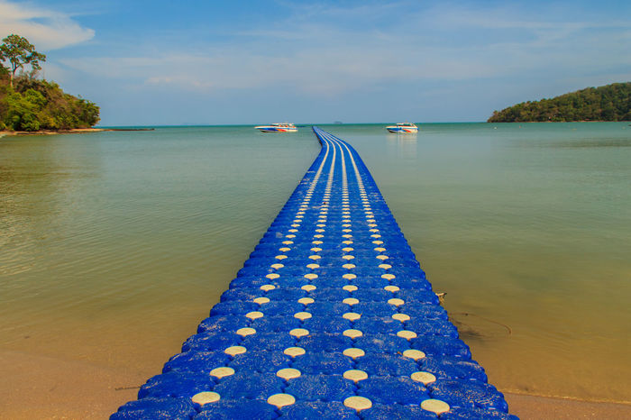 Beautiful blue pontoon made from plastic floating in the sea, rotomolding jetty, a landing stage or small pier at which boats can dock or be moored, floating pier Pier Pontoon Bridge Beauty In Nature Blue Blue Sky Day Floating Floating On Water Floating Pier Jetty Jetty Ocean Sky Jetty, Pier Landing Stage Nature No People Outdoors Pontoon Rotomolding Jetty Scenics Sea Sky Small Pier Water