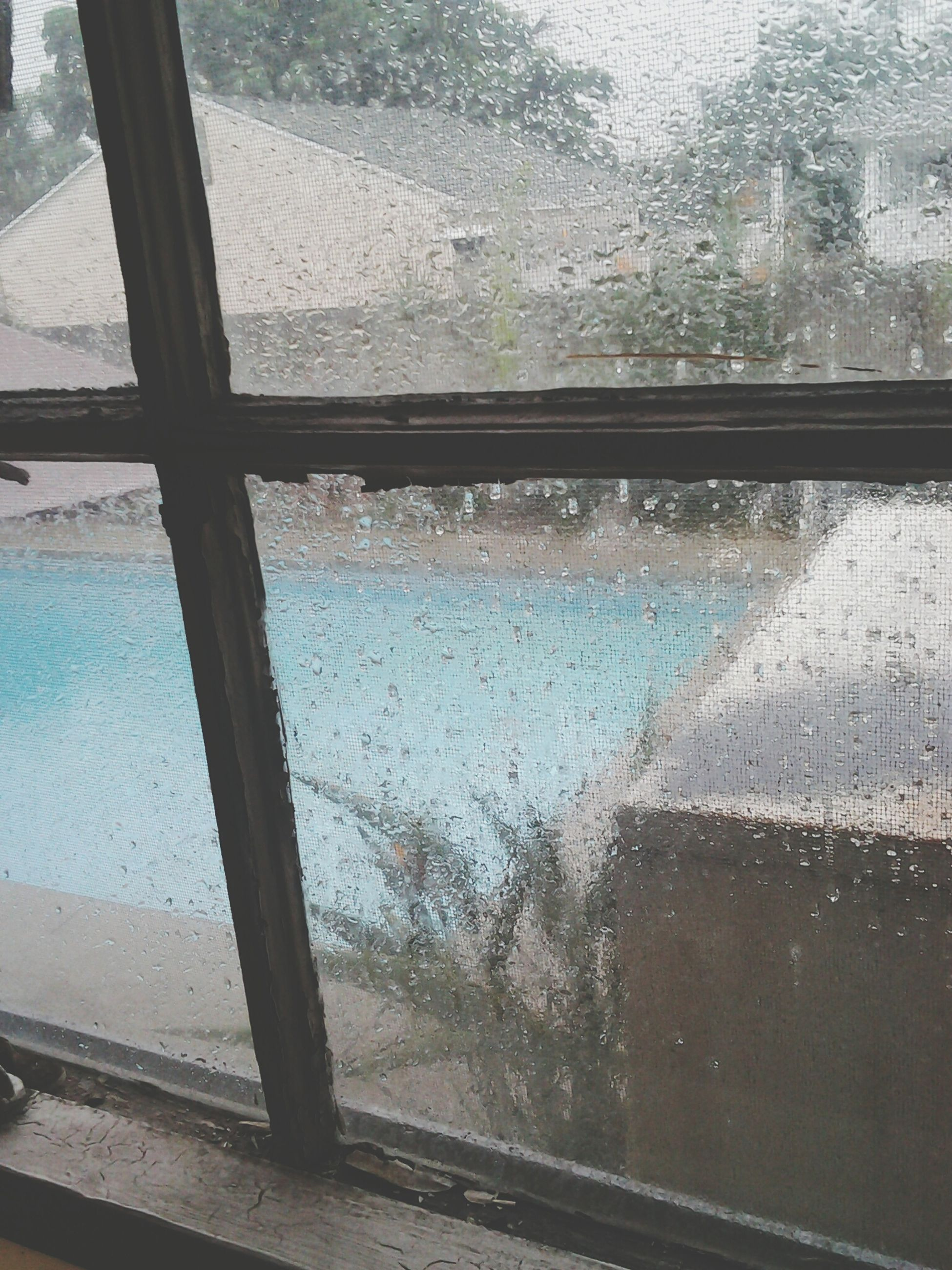 window, glass - material, transparent, water, indoors, drop, wet, looking through window, glass, close-up, rain, reflection, day, raindrop, full frame, no people, window sill, built structure, focus on foreground, backgrounds