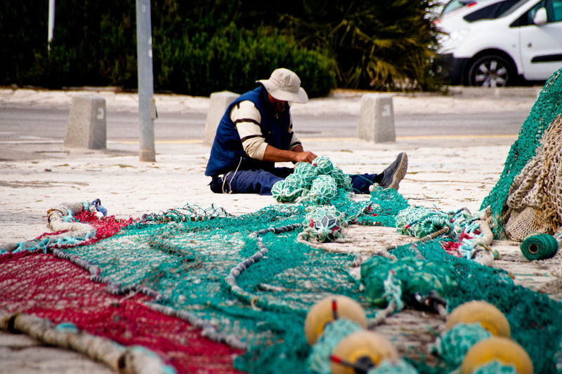 Man making fishing nets and buoys outdoors