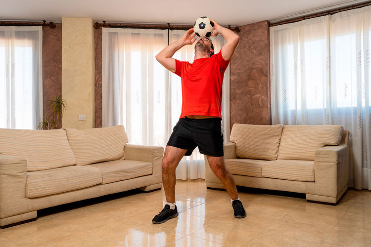 Full length of man standing on sofa at home