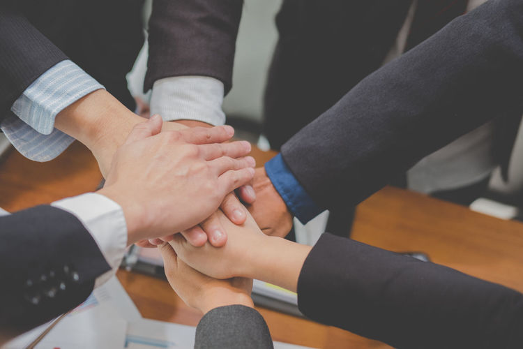 Midsection Of Business Colleagues Stacking Hands While Working In Office