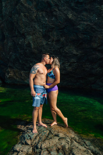 Young couple kissing while standing on rock by sea